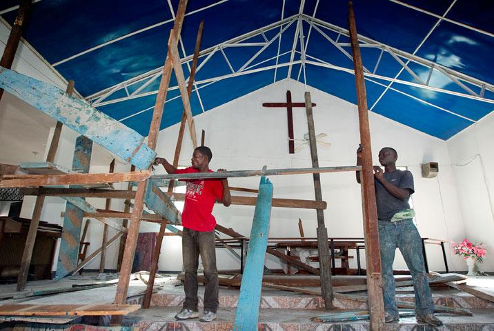 Jean Vixommol (left) and Cerant Wichtlander erect scaffolding to make repairs inside the sanctuary of the Methodist church in Petit-Goâve.