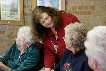 The Rev. Kathy Hammond visits with nursing home residents after a weekday Bible study in Kenmare, N.D. A UMNS photo by Jan Snider.