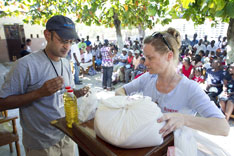Sharad Aggarwal (left) and Melissa Crutchfield of UMCOR unpack a food ration in Mellier, Haiti.