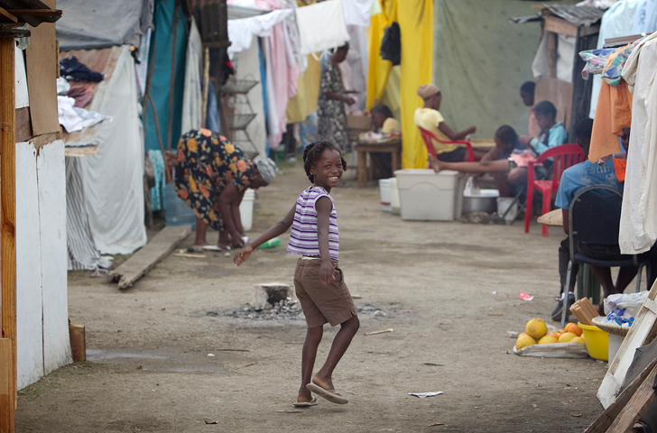 A girl plays between rows of makeshift homes at a temporary camp in the soccer stadium at Leogane, Haiti. A UMNS photo by Mike DuBose.