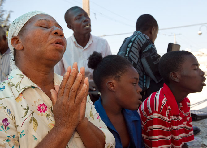 Noel Zierne (left) prays during worship outside St. Martin Methodist Church in Port-au-Prince.  A UMNS photo by Mike DuBose.