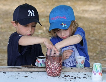 Two kids plant seeds at the Children's Pow Wow in Houston in 2009. A UMNS photo by Ronny Perry.
