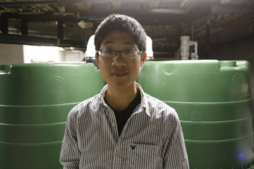 Kelvin Gu, student president of the Duke Smart Home Program, stands in front of storage tanks used to collect and distribute recycled rainwater.