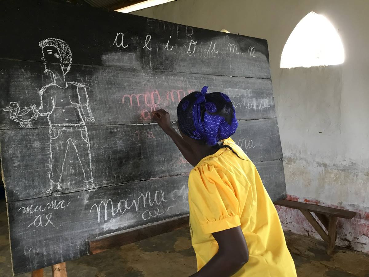 A woman writes on a chalkboard during training provided for the wives of theology students at Kindu United Methodist University in the Democratic Republic of Congo. The seminary students are often accompanied by their spouses, and classes in literacy, cooking and sewing support the women in their future role as pastors' wives. Photo by Judith Osongo Yanga, UMNS.