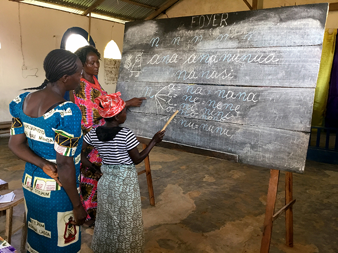 Three of the students work on vowels at a chalkboard during training for the wives of theology students at Kindu United Methodist University in Democratic Republic of Congo. Photo by Judith Osongo Yanga, UMNS.