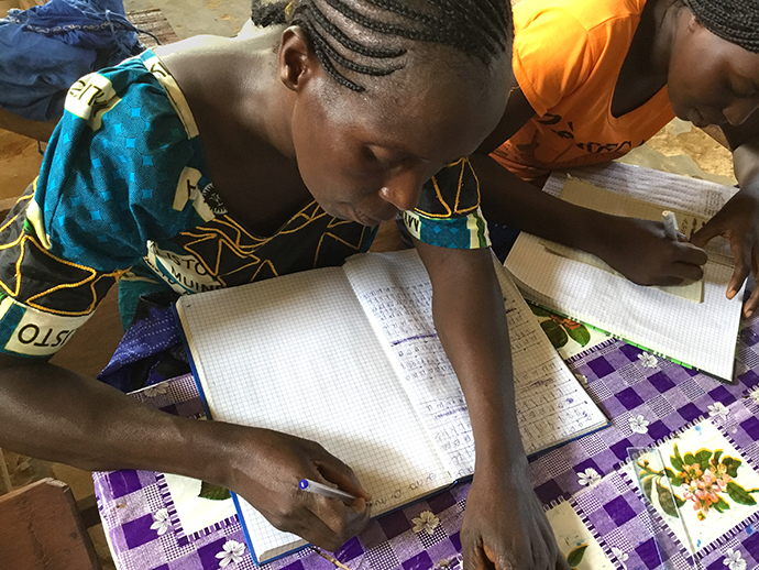 Two women write in notebooks during training provided for the wives of theology students at Kindu United Methodist University in Democratic Republic of Congo. Photo by Judith Osongo Yanga, UMNS.
