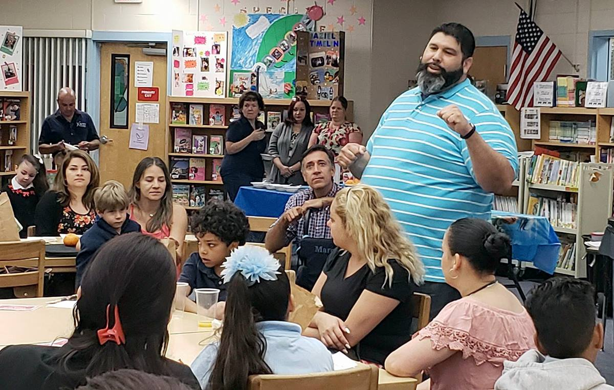 The Rev. Jose Nieves (standing, foreground) meets at Boggy Creek Elementary with families who were displaced from Puerto Rico by Hurricane Maria and have relocated to Kissimmee, Fla. Photo by Linda Logston.