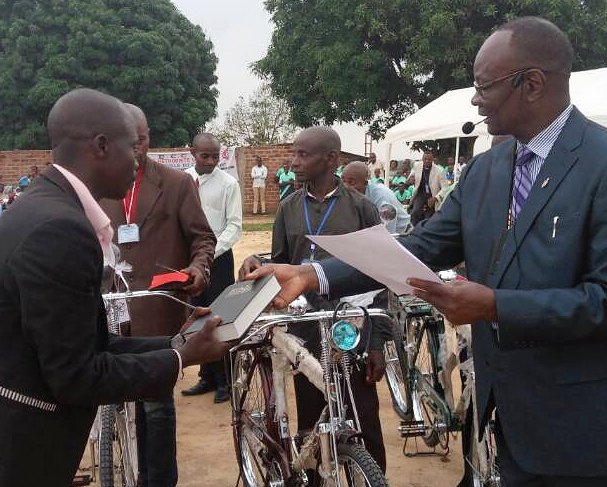 Bishop Gabriel Yemba Unda (right) gives a Bible to a United Methodist pastor in Kindu, Congo, as part of the church's Bikes and Bibles ministry to help pastors make disciples in inaccessible areas. Photo by Judith Osongo Yanga, UMNS.