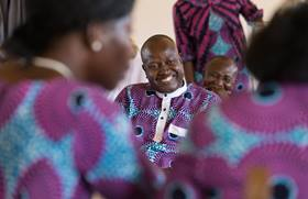 Jonas Assogba (center) grins as he tries to answer a question during a church version of the newlywed game at Nazareth United Methodist Church in Abidjan, Côte d'Ivoire. The game marked the completion of a three-and-a-half month course on marriage. Photo by Mike DuBose, UMNS.