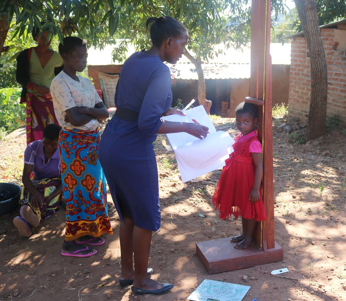 Agness David, 4, is measured for weight and height in Malawi where many children suffer from malnutrition. She is receiving nutritional support through the help of the Malawi United Methodist Church. Photo by Francis Nkhoma, UMNS.