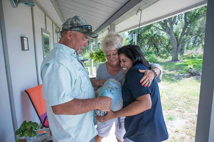 Kim and Donna Hines of Rockport, Texas, who lost their home in Hurricane Harvey, accept a quilt from Zelina Alvarado, a case management worker from the Rio Texas Conference. The conference was able to find financing and volunteer labor that helped the couple make a new home from their garage and a second structure on their property. Photo courtesy of the Rio Texas Conference.