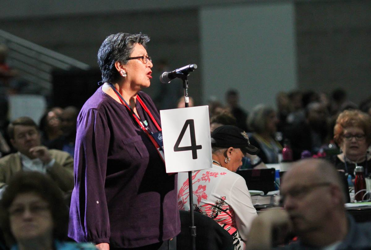 "Cynthia Kent, chairperson of the Native American International Caucus, speaks on a petition that asks The United Methodist Church ""to be intentional about raising awareness of the harm caused by some sports teams through the use of mascots and/or symbols promoting expressions of racism and disrespect of Native American people,"" during the May 19 plenary session of the 2016 General Conference in Portland, Ore. Photo by Maile Bradfield, UMNS."