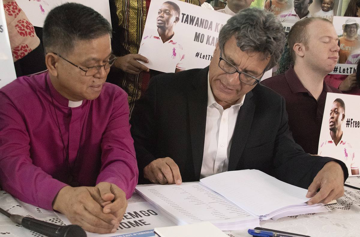 Thomas Kemper (center), top executive of the United Methodist Board of Global Ministries, shows Philippine Bishop Ciriaco Q. Francisco a list of people calling for the release of two missionaries during a press conference at Good Samaritan United Methodist Church in Manila, Philippines, July 2. Photo by Jan Snider, UMCom.