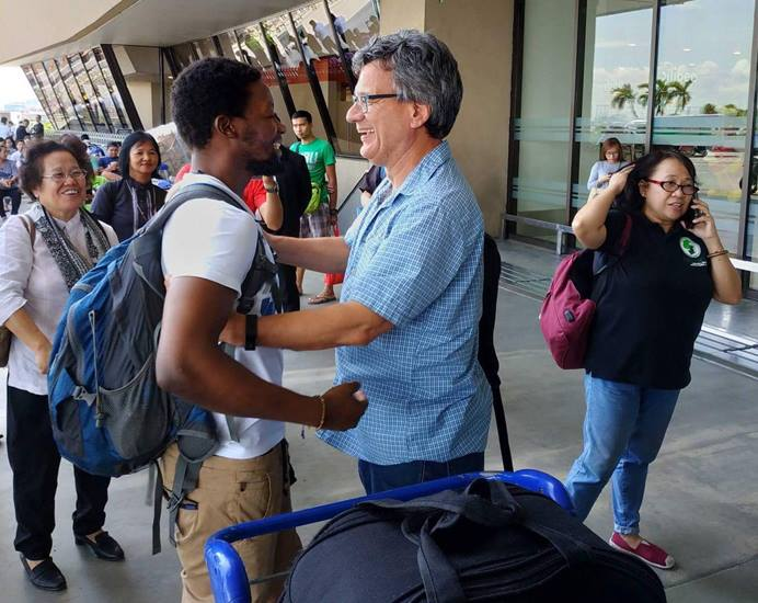 United Methodist missionary Tawanda Chandiwana (left foreground) is embraced by Thomas Kemper, head of the denomination's Board of Global Ministries, at the Ninoy Aquino International Airport in Manila, Philippines, after Chandiwana was released from a detention center and allowed to leave the country. Photo by Mendoza Adrian.