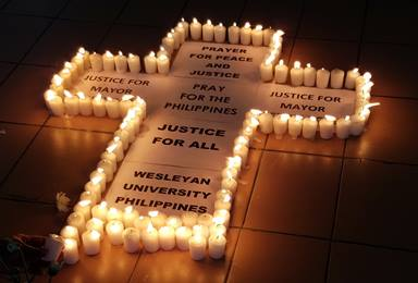 A cross with candles calls for justice and peace at a prayer vigil led by the Rev. Francis Fajardo at Wesleyan University-Philippines for slain mayor, Ferdinand Bote. Bote, mayor of the General Tinio in Nueva Ecija province, was gunned down July 3. Photo courtesy of Clarafe Gonzales & Sergio Arevalo.
