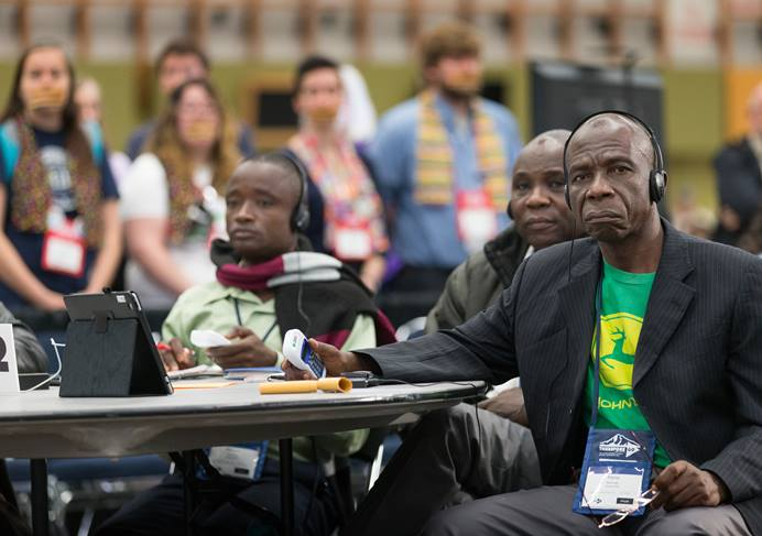 Delegate Pierre Kasongo (right) and other members of the Tanganyika delegation vote on legislation while listening to a translation of the 2016 General Conference proceedings. The Commission on General Conference said translations of the Way Forward proposals are coming. File Photo by Mike DuBose, UMNS.