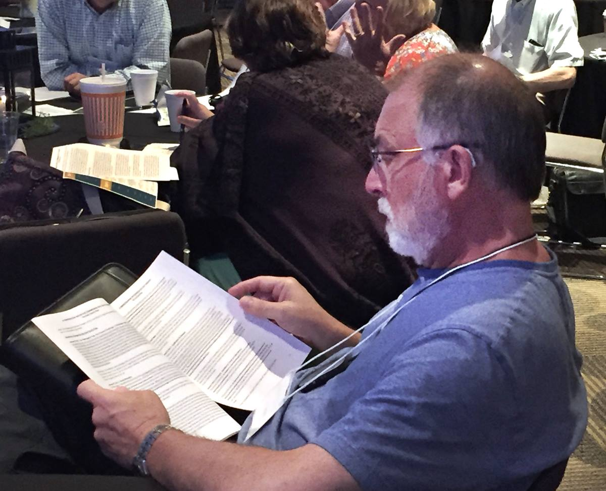 Rev Tom Steagald of Hawthorne Lane United Methodist Church in Charlotte,  North Carolina reads the  One Church plan during break at Uniting Methodists meeting July 17 in Dallas. Photo by Sam Hodges, UMNS