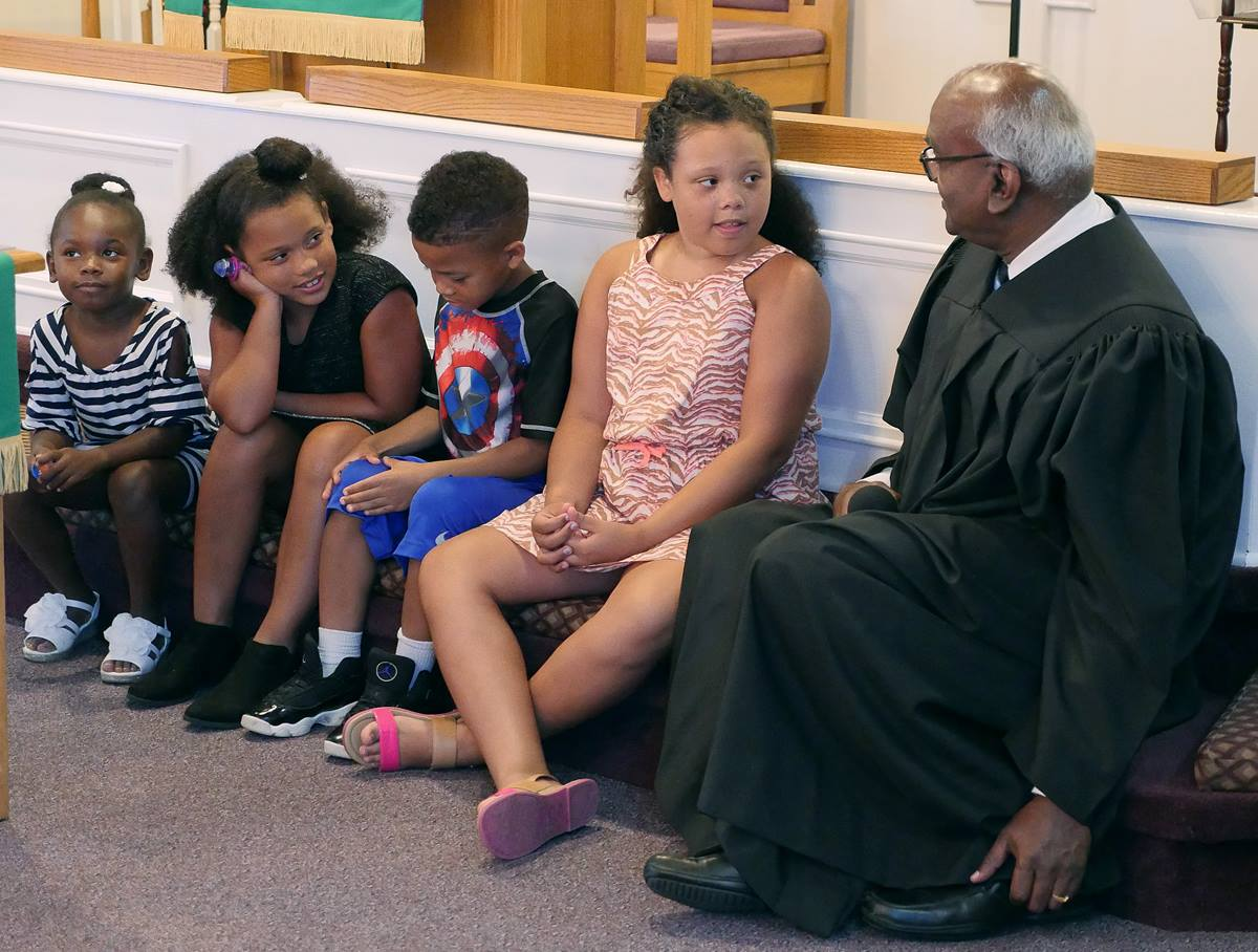 The Rev. Moses Kumar shares a children's sermon on July 8, his second Sunday as pastor of Lillard Chapel United Methodist Church in Murfreesboro, Tennessee. The top executive of the denomination's finance agency, he is also a newly licensed local pastor. Photo by Heather Hahn, UMNS.