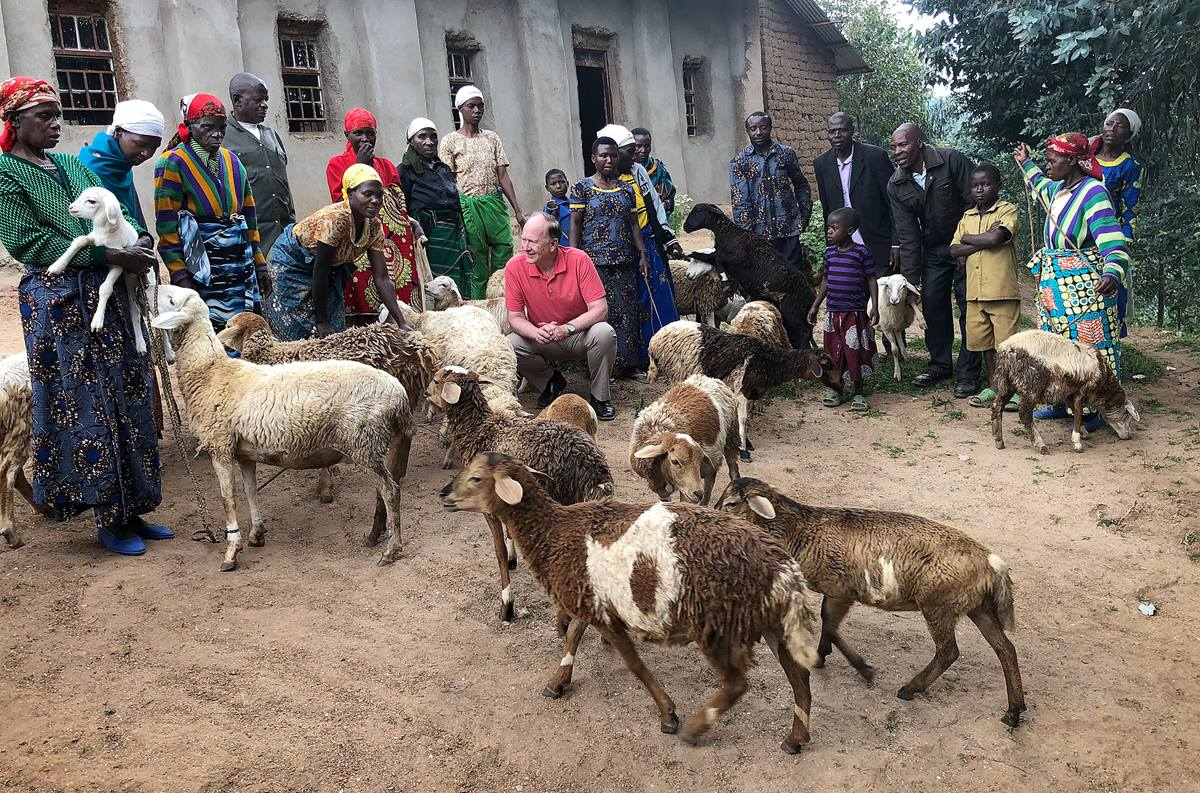 The Rev. Donald E. Messer (kneeling) meets some of the 60 Rwandan women who received sheep from the Colorado-based Center for Health and Hope. The sheep were purchased by individuals in the U.S. as Christmas gifts in honor of their family and friends. Photo courtesy of Donald E. Messer.