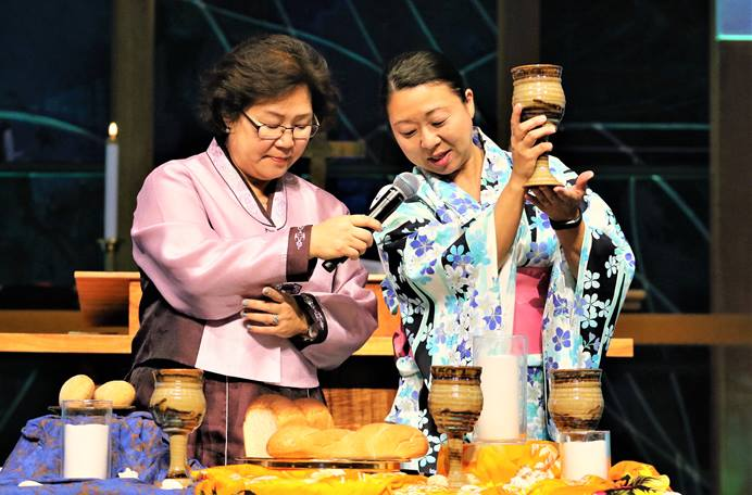 The Revs. Pauline Hyekyoung Kang (left) and Motoe Yamada Foor lead the Holy Communion prayer at the opening worship service of the 2018 Ohana Conference. Photo by the Rev. Thomas Kim, UMNS.