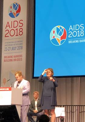 Singer and AIDS activist Elton John speaks during the 2018 International AIDS Conference in Amsterdam as Prince Harry, Duke of Sussex, sits in the background. The two are collaborating on a new HIV/AIDS campaign aimed at reaching young men. Photo by Donald E. Messer.