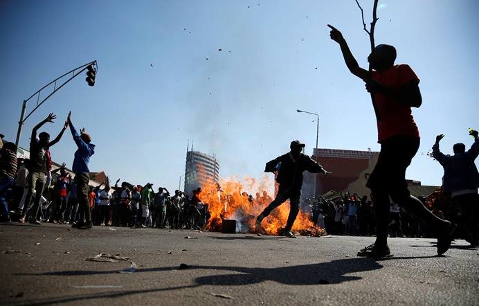 Supporters of the opposition Movement for Democratic Change party block a street on Aug 1 in Harare, Zimbabwe. In the wake of soldiers opening fire on the protesters, United Methodist bishops and other church leaders called for prayers for peace. REUTERS/Siphiwe Sibeko. Do not reuse. One Time Use.