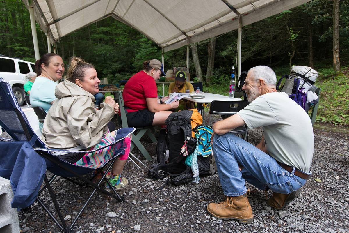 The Rev. Alan Ashworth (right) visits with Appalachian Trail thru-hikers at a free hiker feed sponsored by New Hope Union United Methodist Church near Bastian, Va. Volunteers set up a temporary shelter where the trail crosses a gravel parking area and offered hot sandwiches, salads and cold drinks to weary hikers. Photo by Mike DuBose, UMNS.