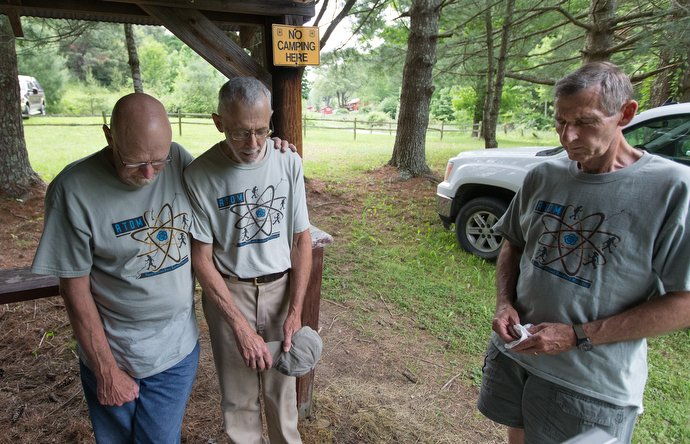 The Rev. Alan Ashworth (center) prays with volunteers Greg Floyd (left) and Herrn Northcutt as they finish up a free hiker feed for Appalachian Trail thru-hikers near Ceres, Va. The volunteers are from Highland Valley United Methodist Church in Little Rock, Ark. Photo by Mike DuBose, UMNS.