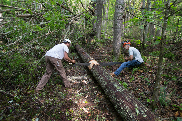 Joe Thompson (left) and the Rev. Alan Ashworth use a two-person crosscut saw to remove a fallen tree across the Appalachian Trail near Bastian, Va. Power tools are not permitted in designated wilderness areas, requiring the use of the well-worn hand saw. Photo by Mike DuBose, UMNS.