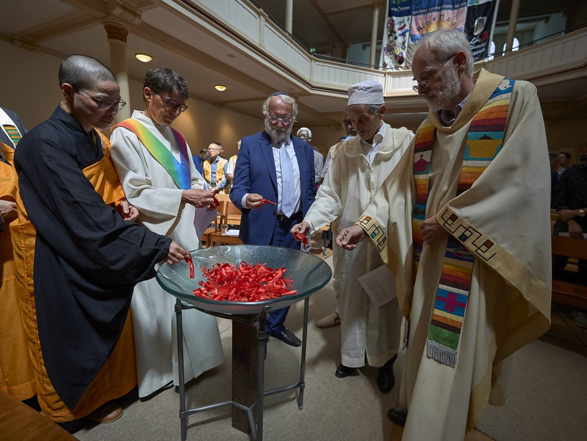 Religious leaders from several traditions collected red ribbons, a sign of hope amid the HIV crisis, to place on a symbolic bridge during a July 23 interfaith prayer and memorial service in the Keizersgrachtkerk in Amsterdam. Sponsored by the World Council of Churches' Ecumenical Advocacy Alliance, the service was held on the first day of the 2018 International AIDS Conference. Photo by Paul Jeffrey.