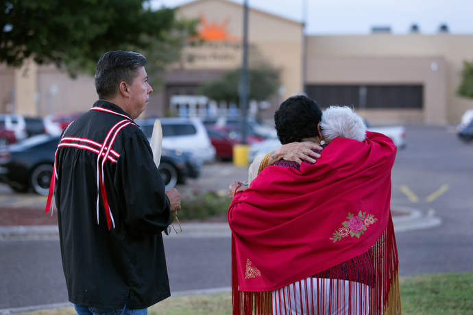 The Rev. Donna Pewo (wearing red shawl) embraces Henrietta Mann following a prayer service for immigrant children held at the Casa Padre detention center, visible behind them. At left is the Rev. David Wilson, superintendent of The United Methodist Church's Oklahoma Indian Missionary Conference. Photo by Mike DuBose, UMNS.