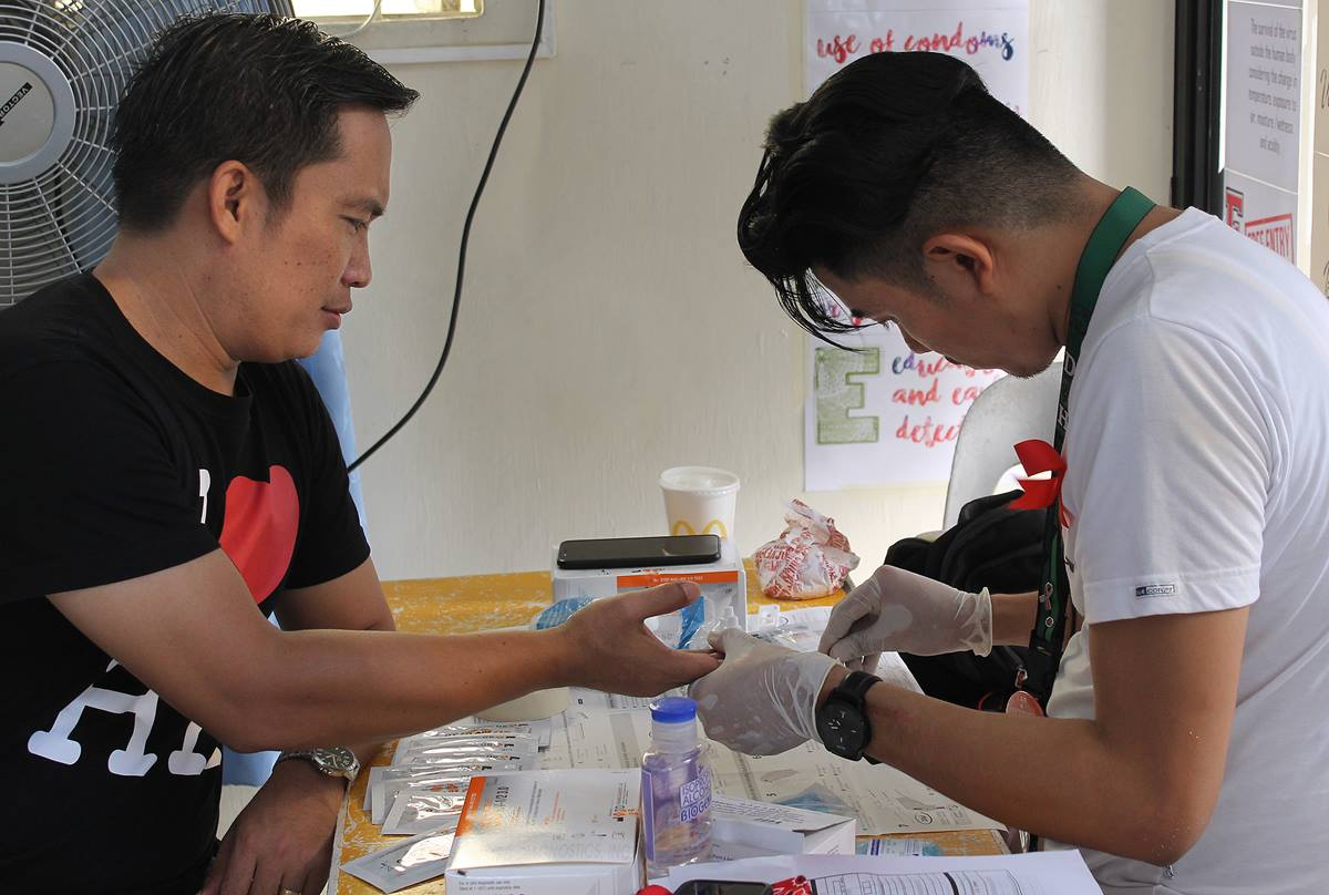 The Rev. Jeremias Dumaya (left) has blood drawn for HIV screening during a symposium on HIV and AIDS education at Wesleyan Third Millennium United Methodist Church in Cabanatuan City, Philippines. Photo by Gladys Mangiduyos, UMNS.
