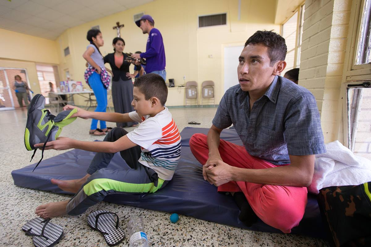 Oliver (right) and his 8-year-old son Anthony rest at an overflow shelter for recent immigrants at the Basilica of Our Lady of San Juan del Valle in McAllen, Texas. They fled their native Honduras in fear of gang violence and asked that their real names not be used.