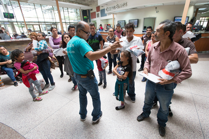 Eli Fernandez (center) helps direct immigrants inside the bus station in McAllen. Photo by Mike DuBose, UMNS.
