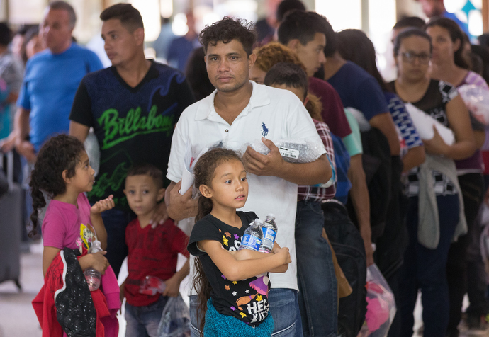 Bewildered immigrants who have just been released from a U.S. Border Patrol detention facility clutch water bottles and personal belongings while they wait in line at the bus station in McAllen, Texas. Photo by Mike DuBose, UMNS.