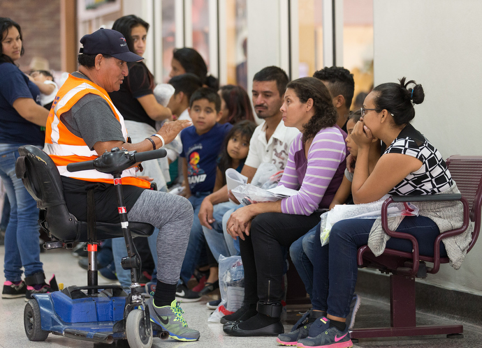 Volunteer Luis Guerrero (on scooter) gives immigrants a lesson in how to navigate the U.S. bus system at the station in McAllen, Texas. Guerrero is an ex-firefighter who lost one of his legs in the line of duty. He comes to the bus station almost every day to help. Photo by Mike DuBose, UMNS.