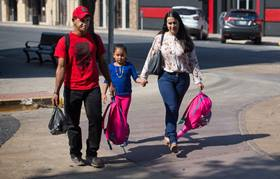 Catholic Charities volunteer Maria Peña (right) leads Honduran immigrants Isaác Rivera Ramos and his daughter Katerin to the bus station in McAllen, Texas. Photo by Mike DuBose, UMNS.