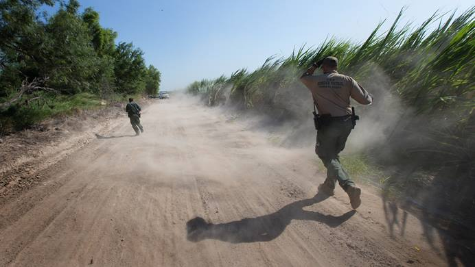 U.S. Border Patrol agents run down a dirt road amid swirling dust stirred up by a helicopter during a search for people who had crossed into the United States illegally and were hiding in heavily wooded areas and sugar cane fields near McAllen, Texas. Photo by Mike DuBose, UMNS.