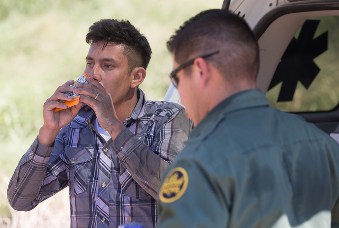 Border patrol agents come to the aid of a fellow agent who became overheated while searching a sugarcane field for people who entered the U.S. illegally. Photo by Mike DuBose, UMNS.