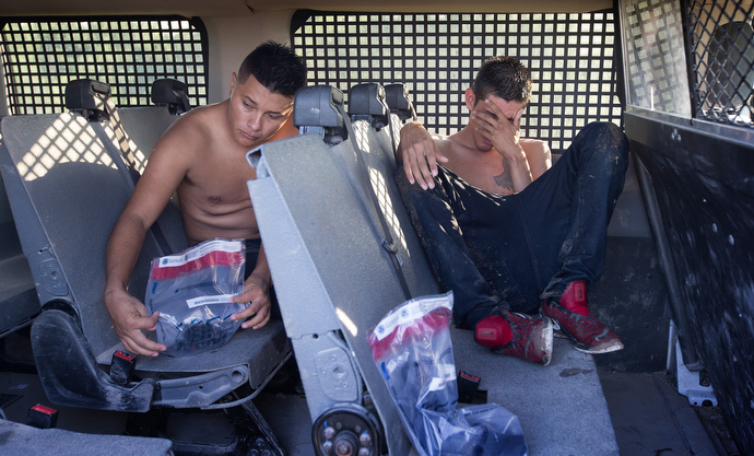 Coyotes who were caught smuggling people across the Rio Grande into the U.S. sit in the back of a Border Patrol paddy wagon near McAllen. After being searched for weapons and contraband, they placed their belongings, including their shoelaces, into plastic bags for safekeeping while their cases are adjudicated. Photo by Mike DuBose, UMNS.