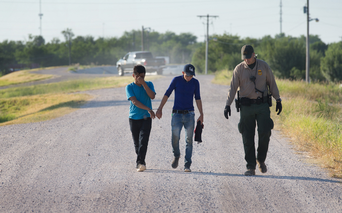 A U.S. Border Patrol agent escorts two young men who were caught entering the U.S. illegally. Photo by Mike DuBose, UMNS.