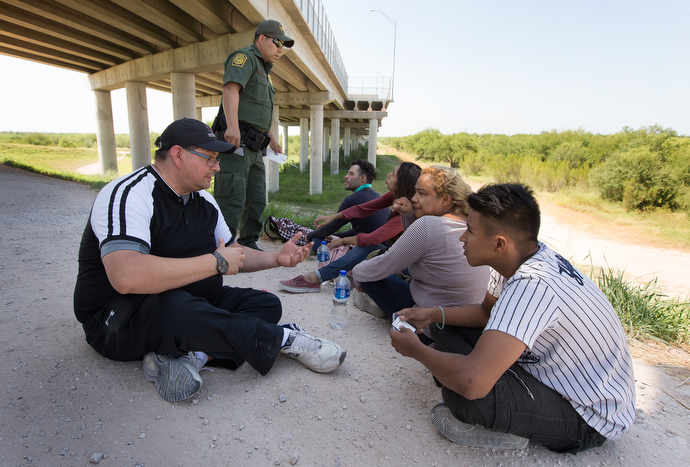 The Rev. Robert Lopez (left) visits with a group from El Salvador and Guatemala who were caught entering the U.S. illegally by crossing the Rio Grande near McAllen. Lopez, superintendent of The United Methodist Church's El Valle and Coastal Bend Districts in the Rio Texas Conference, said the group had been traveling for a month to reach the U.S. Photo by Mike DuBose, UMNS.