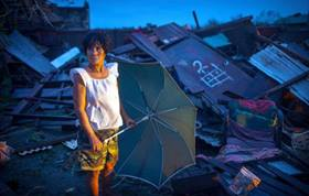 An unidentified woman stands by a collapsed building struck by Typhoon Mangkhut in the Philippiines.  Photo courtesy of Cagayan provincial information office.