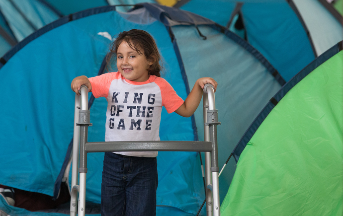 A child plays with a relative's walker amid rows of camping tents that provide some privacy for families at the Movimiento Juventud 2000 shelter. Photo by Mike DuBose, UMNS.