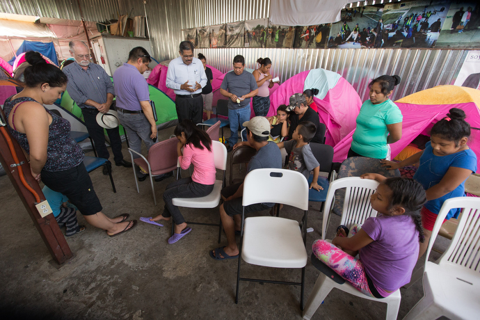 Bishop Felipe Ruiz Aguilar of the Methodist Church of Mexico (fourth from left) leads a prayer with families and visiting United Methodists at the Movimiento Juventud 2000 shelter. Photo by Mike DuBose, UMNS.