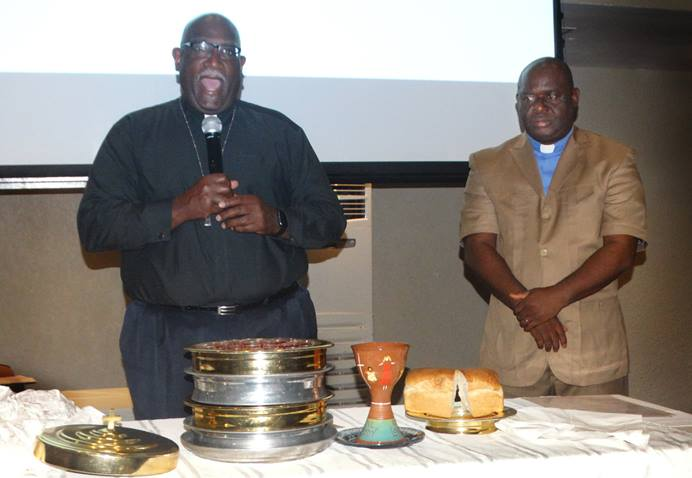 Bishop Gregory V. Palmer (left) of the Ohio West Area and the Rev. James Boye-Caulker of Sierra Leone bless the elements of Holy Communion during closing worship for the Africa Comprehensive Plan meeting in Freetown, Sierra Leone. Photo by Phileas Jusu, UMNS.