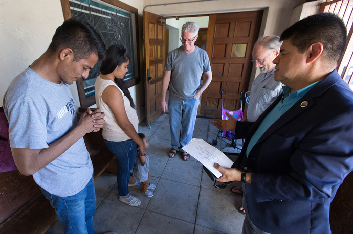 The Rev. Joel Hortiales (right), a United Methodist missionary with the Board of Global Ministries, leads a prayer with Jose Antonio Marchas Novela (left), his wife, Irlanda Lizbeth Jimenez Rodriguez, and their 1-year-old son, Jose Antonio, at the Christ United Methodist Ministry Center. Joining the prayer are the Revs. John Fanestil (center) and David Farley. Photo by Mike DuBose, UMNS.