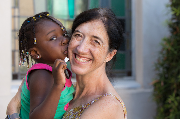 Volunteer Kathryn LaPointe gets a kiss from Haley, 4, a recent immigrant from Benin in West Africa, who is staying at Christ United Methodist Ministry Center. Photo by Mike DuBose, UMNS.