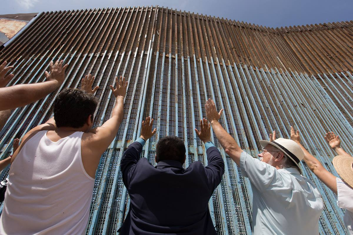 The Revs. Joel Hortiales (center, in blue blazer) and David Farley (to Hortiales' right) join parishioners of the Border Church in Tijuana, Mexico, as they lift their arms skyward beneath the fence that marks the border with the U.S.