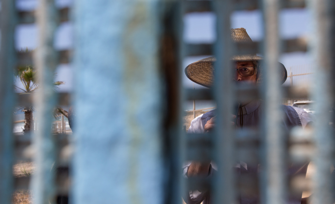 The Rev. John Fanestil, A United Methodist pastor, is visible through the steel mesh of the U.S. - Mexico border fence as he helps lead a cross-border service of Holy Communion from Friendship Park near San Diego on the U.S. side. Photo by Mike DuBose, UMNS.